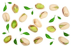 Pistachios decorated with green leaves isolated on white background, top view. Flat lay pattern