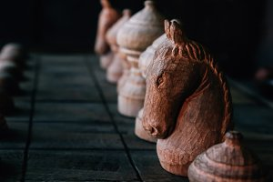 Close up of chessboard with chess pieces and horse in front - strategic and outwit game play competition concept
