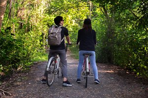 Couple of young man and woman riding a bicycle for adventure and leisure trekking activity in the countryside forest - active and fitness together concept