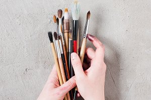 Woman's hands holding the brushes