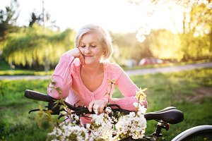 Beautiful senior woman with bicycle outside in spring nature.