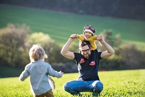 A father with his toddler children having fun outside, spring nature.
