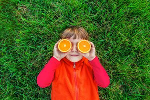 Child on green grass with oranges.