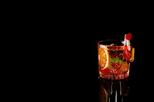 Blood Orange Margarita coctail with ice and mint on black