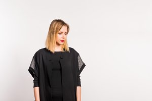 Portrait of a young beautiful woman with black clothes in studio on white background.