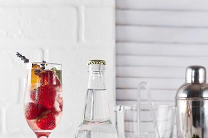 Red Cocktail with ice and strawberry, ginger and lavender with a bottle of tonic and a place under the text on the bottle on wooden background
