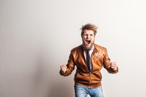 Portrait of a young hipster man in a studio, screaming. Copy space.
