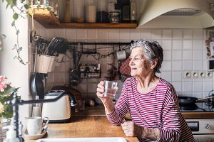 An elderly woman standing in the kitchen, holding a glass of water.