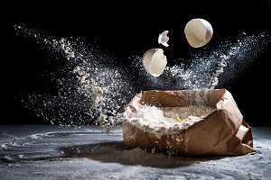 Flour and egg on black background