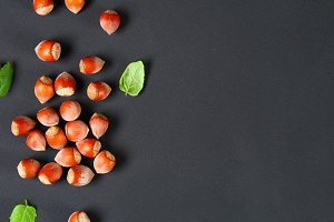 Top view of roasted peeled hazelnuts on a saturated black background.Snacks. Top view. Copy space.