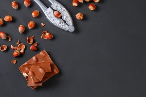 Chocolate with hazelnuts, mint and grains of coffee on a dark gray table. Top view. Copy space.