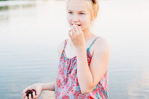 blond girl eating cherry