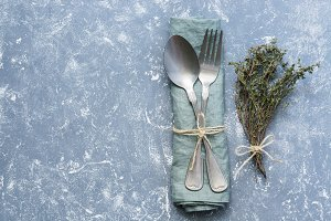 Rustic vintage set of fork and spoon on a gray background with a bouquet of dried thyme. Place for text.