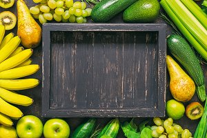 Background of fresh vegetables and fruits with an empty wooden tray. Frame of yellow and green vegetables. A top view, a place for your text or advertising.