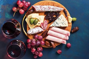 Delicious appetizers with red wine on a blue background. Fruit, cheese, ham, sausage. Top view, flat lay