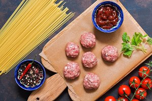 Raw meatballs and spaghetti on a blue-brown background, top view.