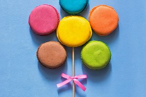 Flower of multicolored macaroons. Blue painted background. The concept of a holiday.