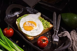Sandwich with fried egg and avocado on a dark background, rustic style.
