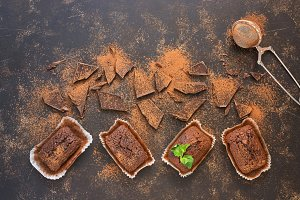 Chocolate muffins with chocolate slices sprinkled with cocoa powder on a dark background, top view.