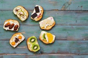 Sandwiches with a variety of filling on a green wooden rustic background. View from above. Sweet sandwiches.