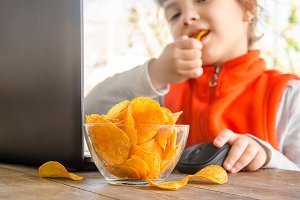 child with chips behind a computer.
