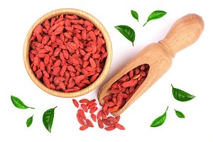 Dried goji berries in wooden bowl and scoop decorated with green leaves Isolated on white background