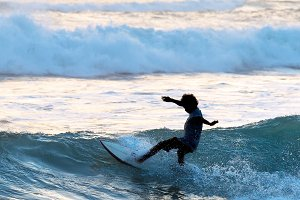 Surfer surf in the ocean at sunset