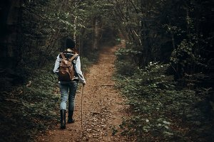 hipster traveler walking in forest