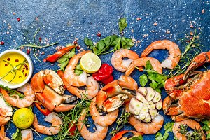 Baner. Fresh raw seafood - shrimps and crabs with herbs and spices on blue background. Copy space