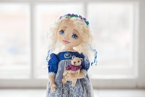 Portrait of textile handmade vintage doll with blue eyes, long blond hair in old blue textile dress with gentle print, in white shirt with purple boots on white background. She holding little textile teddy bear