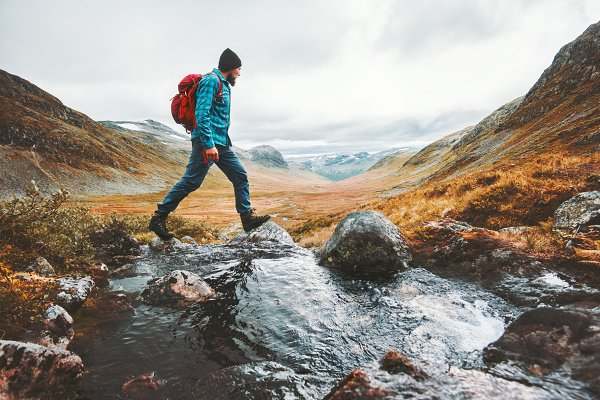 Stock Photos: e v e r s t - Man solo traveling backpacker hiking