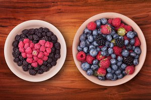 Plates with berries on the wooden table