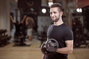 one man, one arm dumbell exercise, smirking, in gym. Unrecognizable group of people behind.