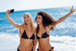 Two women taking selfie on beach