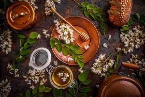 Jar of honey with flowers of acacia