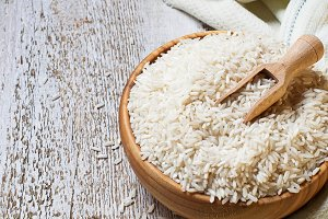 Uncooked rice in a wooden bowl