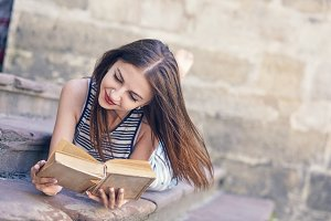 Young attractive girl studying and reading a book on a wooden floor
