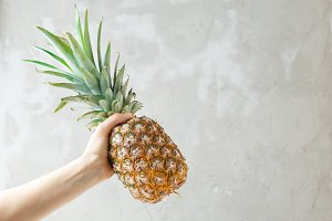 Female hand holding a pineapple