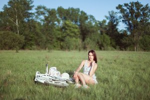 Young woman sits in the grass on a m