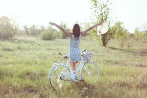 Young woman leaned on her bicycle.