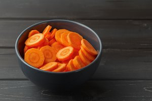 Sliced carrots in a bowl on black