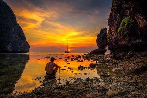 Young boy enjoys dramatic sunset at Maya beach in Thailand