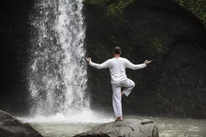 Man standing in meditation yoga on rock at waterfall