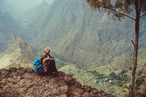 Female sitting in front of breathtaking panorama of deep lush ribeira surrounded by towering peaks. Verdant Xo-Xo valley on Santo Antao Island Cape Verde