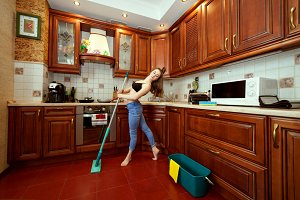 Woman washes the floor with a mop.
