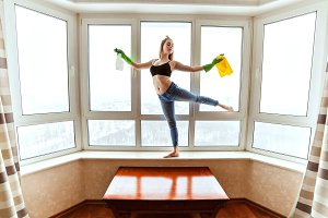 Woman dancing washes the windows.