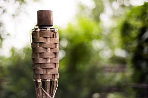 Close-up of traditional bamboo torches oil lamp on nature background.