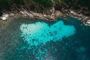 Aerial view of sailing boat next to reef in blue lagoon. Bird eye view