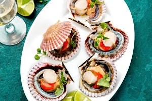 Raw opened shellfish scallops on white plate served with lemon and white wine, turquoise background. Top view. Seafood concept