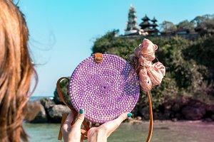 Woman hands with fashionable stylish rattan bag outside. Tropical island of Bali, Indonesia. Rattan and silk.